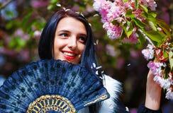 有花、魅力白色毛皮和黑色的妇女 免版税库存图片
