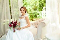 有花佩带的婚姻的白博士花束的可爱的新娘  免版税库存照片