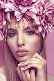 有花冠的美丽的在桃红色背景的妇女和构成 库存图片