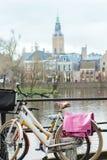 有花卉样式马鞍盖子的荷兰自行车在法院Sint-Jacobskerk背景的池塘和格罗特 免版税库存图片