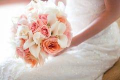有花华美的橙色和桃红色婚礼花束的新娘  免版税图库摄影
