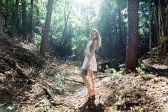 有花和一件白色礼服花束的女孩在一个晴朗的森林里 免版税库存图片