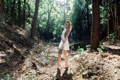 有花和一件白色礼服花束的女孩在一个晴朗的森林里 免版税库存照片