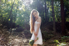 有花和一件白色礼服花束的女孩在一个晴朗的森林里 库存图片