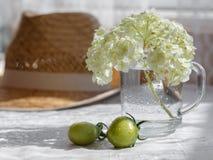 有花和两个未成熟的蕃茄的玻璃杯子在柳条帽子背景 库存图片