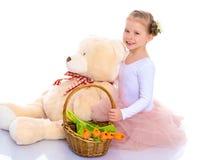 有花和玩具熊篮子的一个小女孩是sitti 免版税库存图片