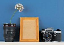 有花和老照相机的花瓶在蓝色wallpap的白色架子 免版税库存图片