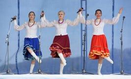 有花圈的三个女孩唱歌在三位一体 库存图片