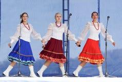 有花圈的三个女孩唱歌在三位一体 免版税库存图片