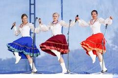 有花圈的三个女孩唱歌在三位一体 免版税图库摄影