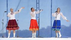 有花圈的三个女孩唱歌在三位一体 库存照片