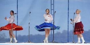有花圈的三个女孩唱歌在三位一体 免版税库存照片