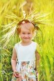 有花圈的美丽的女孩在他的在麦田的头 接近的纵向 库存图片