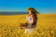 有花圈的美丽的年轻女人在黄色强奸领域风景背景的长的健康头发 Attracive深色的女孩与 免版税库存照片