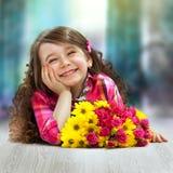 有花大花束的微笑的女孩  免版税图库摄影