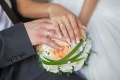 有花婚戒和花束的新娘和新郎的手  免版税图库摄影