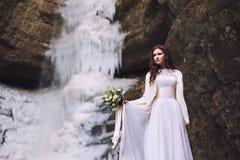 有花婚礼花束的性感的新娘在背景的与冰川和山 免版税图库摄影