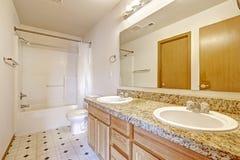 有花岗岩上面、两个水槽和镜子的卫生间镜箱 库存照片