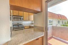 有花岗岩柜台和滑动玻璃门的厨房对阳台 图库摄影
