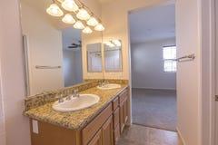 有花岗岩柜台的明亮的公寓主卧室卫生间和在圣迭戈加利福尼亚房地产射击的双水池 免版税库存照片