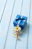 有花木地板的蓝色礼物盒 库存照片