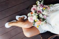 有花束和波浪发样式的性感的美丽的裸体深色的新娘在白色色情内衣 库存图片