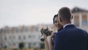 有花束常设外部和微笑的愉快的深色的新娘,白肤金发的新郎接近对女孩和亲吻 衣物夫妇日愉快的葡萄酒婚礼 股票视频