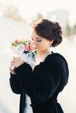 有花束摆在的美丽的新娘室外在雪 免版税库存图片