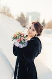 有花束摆在的美丽的新娘室外在雪 库存照片