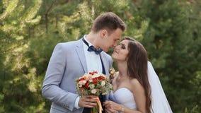有花束的一起迷人的新娘和新郎在绿色自然中 新娘走向新郎从后面并且拥抱 股票录像