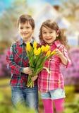 有花束的儿子惊奇为母亲做准备 库存图片