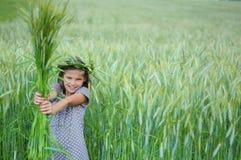 有花束的愉快的小女孩从他的黑麦 库存照片