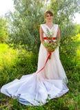 有花束的新娘在有一条红色丝带的一件白色礼服在一棵树附近在夏天 免版税图库摄影