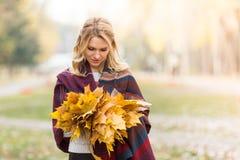 有花束的白肤金发的妇女从槭树叶子 免版税库存照片