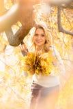 有花束的白肤金发的妇女从槭树叶子 库存照片