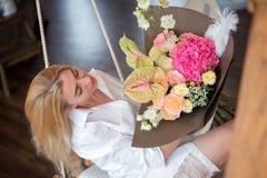 有花束的美丽的女孩在一件白色衬衣 库存照片