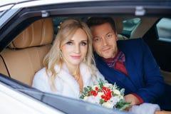 有花束的美女新娘和坐在汽车的一个人,看窗口 库存照片