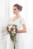 有花束的年轻和美丽的新娘 免版税库存图片