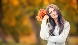 有花束秋叶的年轻可爱的妇女在手中 秋天 库存图片