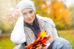 有花束秋叶的年轻可爱的妇女在手中 秋天 库存照片