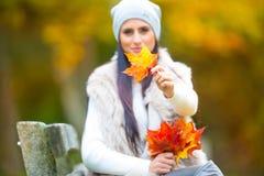 有花束秋叶的年轻可爱的妇女在手中 秋天 免版税图库摄影
