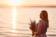 有花架花束的愉快的女孩在海滨的在日落 库存图片