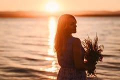 有花架花束的愉快的女孩在海滨的 免版税库存照片