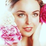 有花牡丹桃红色特写镜头构成软的te的年轻秀丽妇女 免版税库存照片