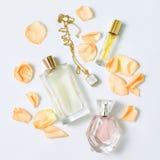 有花瓣的香水瓶在白色背景 香料厂、化妆用品、首饰和芬芳汇集 免版税库存照片