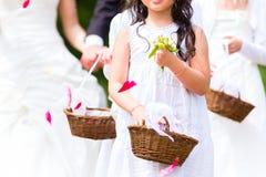 有花瓣篮子的婚礼女傧相 库存照片