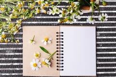 有花白花和bas ket的空白的笔记本在钢净桌上的 免版税库存照片