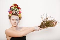 有花的一个少妇在她的头和手 与花的春天图象 有一棵五颜六色的植物的人 女孩和开花 免版税库存照片