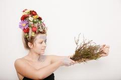 有花的一个少妇在她的头和手 与花的春天图象 有一棵五颜六色的植物的人 女孩和开花 免版税库存图片