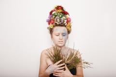 有花的一个少妇在她的头和手 与花的春天图象 有一棵五颜六色的植物的人 女孩和开花 免版税图库摄影